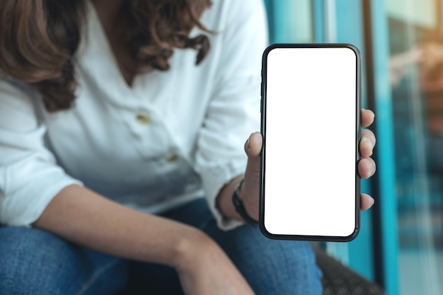Mockupbeeld van een vrouw die zwarte mobiele telefoon met leeg wit scherm in koffie houdt en toont