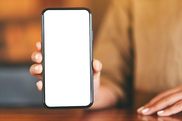 Mockupbeeld van een vrouw die zwarte mobiele telefoon met leeg wit scherm op de lijst in koffie houdt en toont