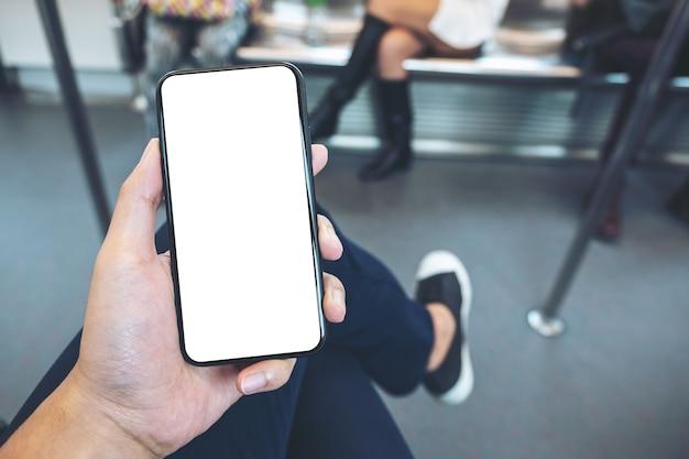 Mockupbeeld van hand die witte mobiele telefoon met leeg zwart scherm in metro houdt