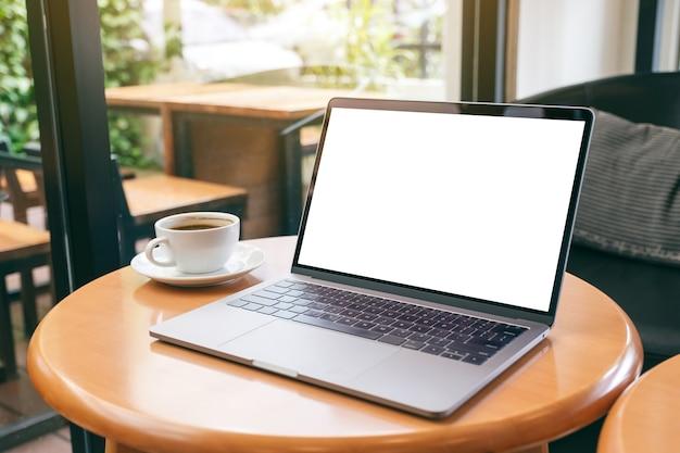 Mockupbeeld van laptopcomputer met leeg wit desktopscherm met koffiekopje op houten tafel