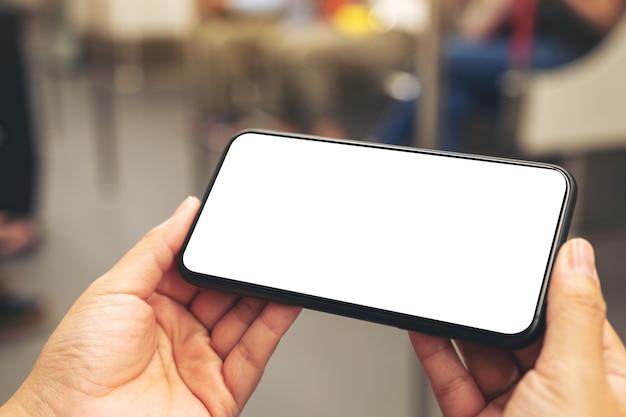 Mockupbeeld van vrouwenhanden die zwarte mobiele telefoon met leeg scherm in metro houden