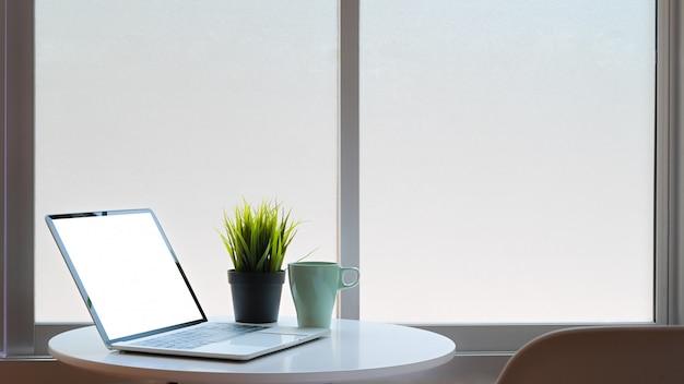Mockuplaptop computer geïsoleerde scherm en koffiemok met plat decoratie op tafel met stoel.
