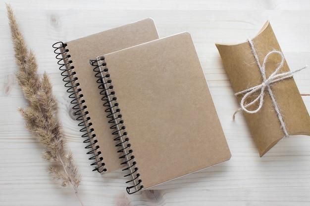 Mockupsamenstelling met twee spiraalvormige notitieboekjes met kraftpapier-omslagen, cadeau-cadeau en donzige droge plant