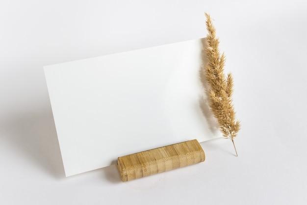Mockupsjabloon met lege lege kaart op houten standaard met droge pluizige plantentak op wit oppervlak.