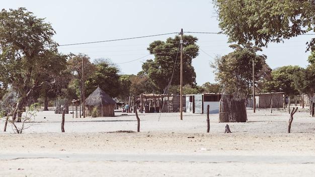 Modderstro en houten hut met rieten dak in de struik. lokaal dorp in de landelijke caprivi-strook, het dichtstbevolkte gebied in namibië, afrika.