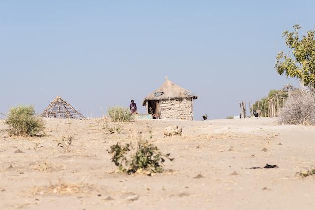 Modderstro en houten hut met rieten dak in de struik
