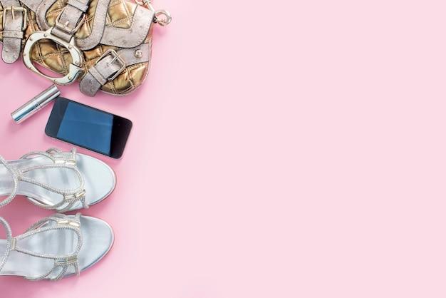 Mode-accessoires schoenen handtas telefoon gadget lippenstift roze achtergrond.