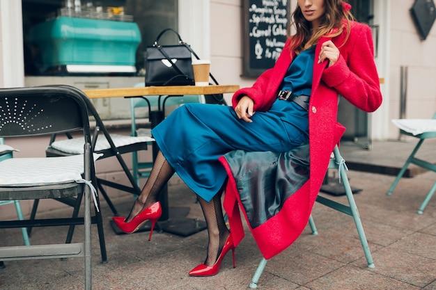 Mode-accessoires van stijlvolle vrouw zitten in stad straat café in rode jas koffie drinken dragen blauwe zijden jurk, schoenen met hoge hakken