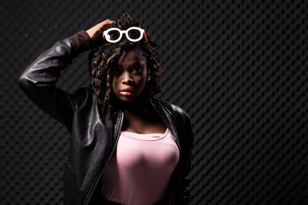 Mode afrikaanse tiener vrouw tan huid zwart afro haar mooie high fashion make-up roze enorme zwarte jas. egg crate studio weinig licht schaduw geluiddicht absorberende muur kamer