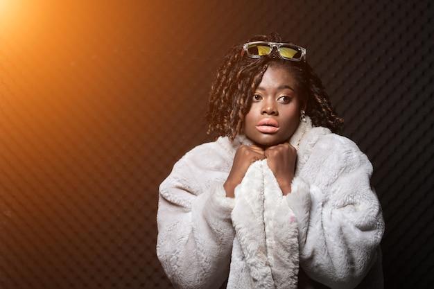 Mode afrikaanse tiener vrouw tan huid zwart afro haar mooie high fashion make-up zonnebril bontmuts jurk. egg crate studio weinig licht schaduw geluiddicht absorberende muur kamer