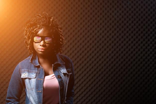 Mode afrikaanse tiener vrouw tan huid zwart afro haar mooie high fashion make-up zonnebril roze uitgestrekte jean jas. egg crate studio weinig licht schaduw geluiddicht absorberende muur kamer