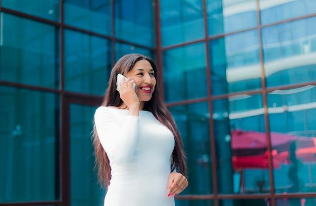 Mode afro vrouw in een luxe witte jurk praten over de telefoon tegen gebouw met blauwe ramen buiten.