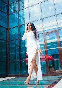 Mode afro vrouw in een luxe witte jurk praten over de telefoon tijdens het wandelen tegen gebouw met blauwe ramen buiten.