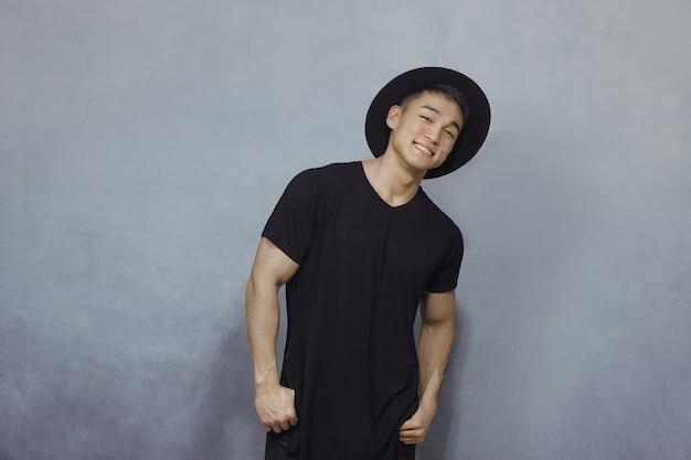 Mode aziatische man in zwarte kleding binnenshuis
