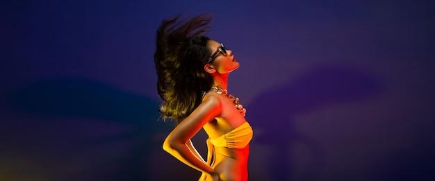 Mode aziatische vrouw tan huid zwart haar mooie high fashion make-up zonnebril parel ketting accessoires dragen gele bikini. studio verlichting donkere rook achtergrond kopie ruimte tekst logo