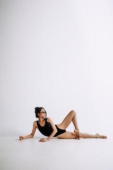 Mode ballet. jonge vrouwelijke balletdanser in zwarte bodysuit tegen witte achtergrond.