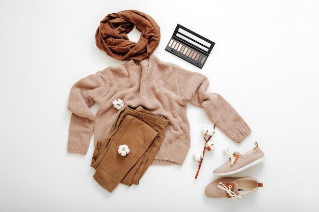 Mode basic vrouwelijke kleding schoenen set beige bruine kleuren gebreide trui sjaal en katoen bloemen cosmetica. plat lag lente winter vrouw vrouwelijke outfit. kleding op een witte achtergrond.