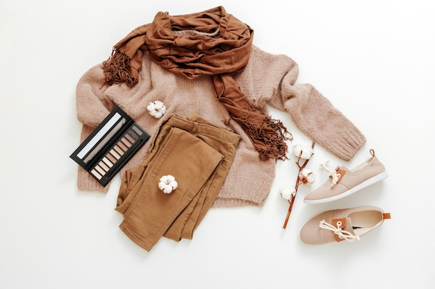 Mode basic vrouwelijke kleding schoenen set beige bruine kleuren gebreide trui sjaal katoen bloemen cosmetica. plat lag lente winter vrouw vrouwelijke outfit. vrijetijdskleding set.