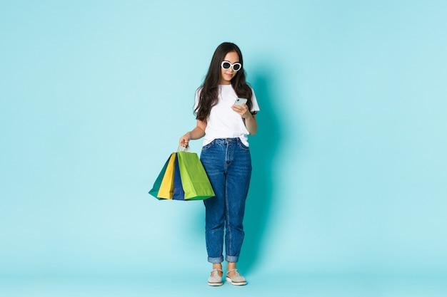 Mode, beauty en lifestyle concept. full-length shot van stijlvolle aantrekkelijke aziatische vrouw met boodschappentassen en met behulp van mobiele telefoon, sms-bericht over lichtblauwe achtergrond.