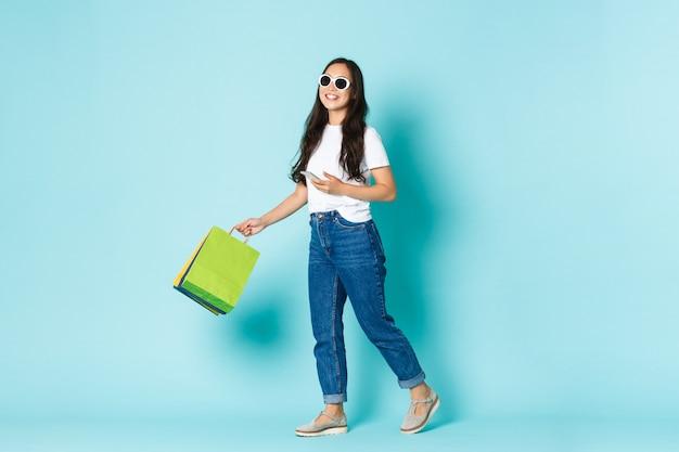 Mode, beauty en lifestyle concept. vrolijke aantrekkelijke lachende aziatische vrouw wandelen in winkelcentrum, winkelen, tassen en smartphone vasthouden, taxi bellen, staande lichtblauwe muur