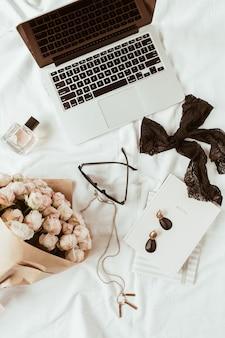 Mode, beauty, lifestyle blogger thuiskantoor werkruimte. laptop, rozenboeket, vrouwelijke accessoires op wit linnen