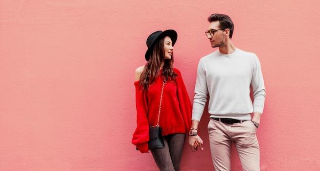 Mode beeld van elegante stijlvolle paar verliefd hand in hand en kijken met plezier naar elkaar. langharige vrouw in rode gebreide trui met haar vriendje poseren.