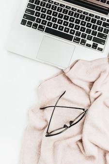 Mode blogger thuisbureau met laptop, bril en trui op wit oppervlak