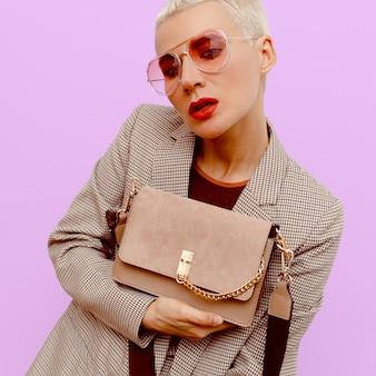 Mode blonde dame in een geruit vintage pak en stijlvolle accessoires bril en clutch