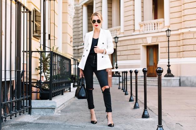 Mode blonde vrouw in zonnebril loopt op straat op hoge hakken. ze draagt een wit jasje en een zwarte gescheurde spijkerbroek.