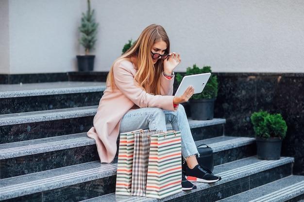 Mode blonde vrouw na het kopen van nieuwe kleren. ze zit met haar laptop op de straattrap in de buurt van de boetiek.