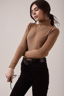 Mode brunette vrouw coltrui en een gouden ketting dragen