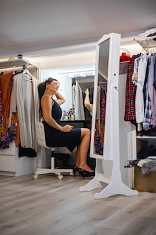 Mode brunette vrouw die accessoires kiest die zich klaarmaken voor een feestgebeurtenis thuis garderobe