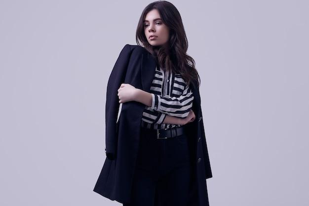 Mode brunette vrouw draagt een gestreepte blouse en een zwarte jas
