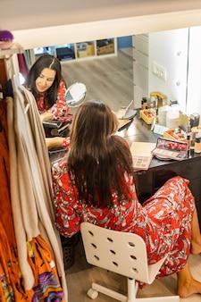 Mode brunette vrouw klaar om te feesten evenement thuis garderobe make-up voor spiegel