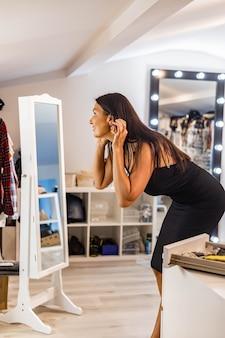 Mode brunette vrouw oorbellen kiezen spiegel kijken klaar om te feesten evenement