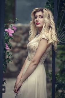 Mode buiten foto van elegante mooie vrouw met blond haar in luxe pailletten jurk, poseren in zomer park