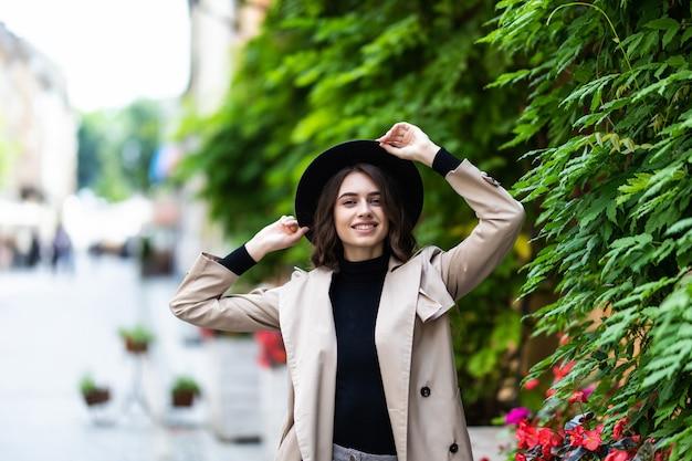 Mode buiten foto van jonge mooie vrouw in elegante outfit en zwarte hoed lopen op straat