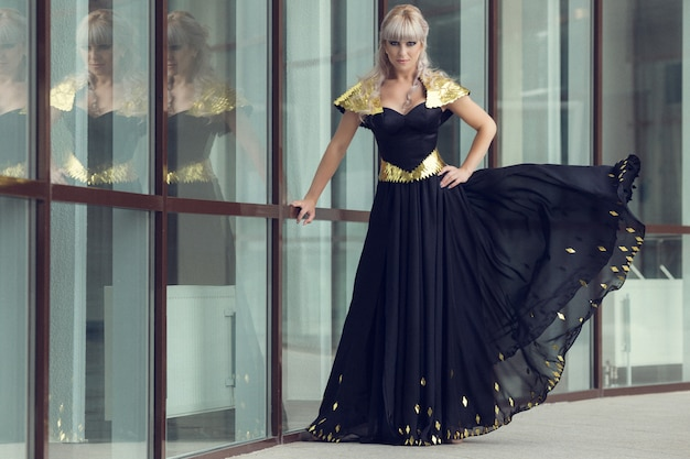 Mode buiten foto van mooie sensuele vrouw met lang haar in luxe pailletten jurk poseren in de zomer stad