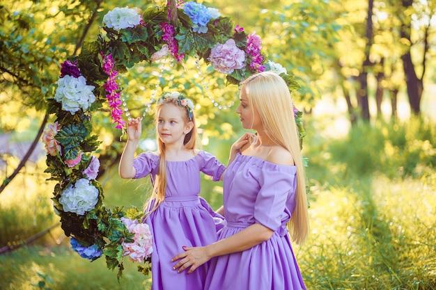 Mode buiten foto van prachtige familie look. mooie moeder met lang donker haar poseren met haar kleine schattige baby in soortgelijke jurken met bloemen print