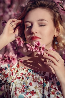 Mode buiten foto van prachtige jonge vrouw in elegante jurk poseren in tuin met bloesem perzikbomen. blond in bloeiende tuinen