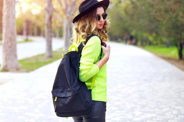 Mode buiten portret van jonge vrij stijlvolle hipster vrouw trendy neon trui zonnebril en vintage hoed dragen, reizen met rugzak. streetstyle herfst herfstlook.