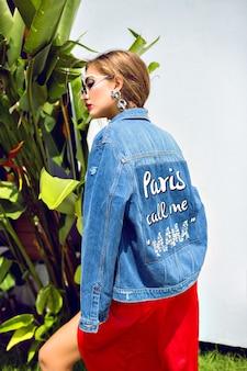 Mode buiten portret van prachtige blonde vrouw, luxe elegante avondjurk, winst zonnebril dragen. en hipsterjack
