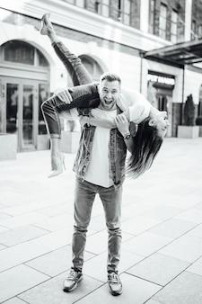 Mode buiten romantisch portret van mooie jonge verliefde paar zoenen en knuffels op straat. stijlvolle herfstoutfit, zwarte leren tas en jas.