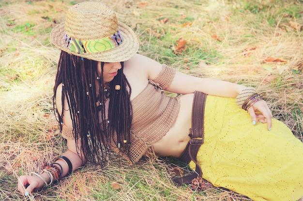 Mode buiten vrouw portret met dreadlocks, gekleed in gebreide top, gele rok en strohoed, rustend op het droge gras in park