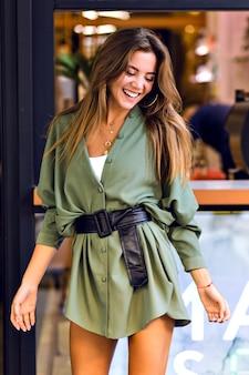 Mode buitenbeeld van stijlvolle jongedame met plezier in de stadsbar, weekendpasteitje, trendy outfit, lange haren, positieve stemming.