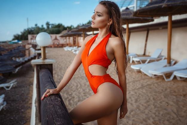 Mode buitenfoto van mooie sensuele vrouw met lang donker haar in elegante oranje zwembroek ontspannen naast zwembad