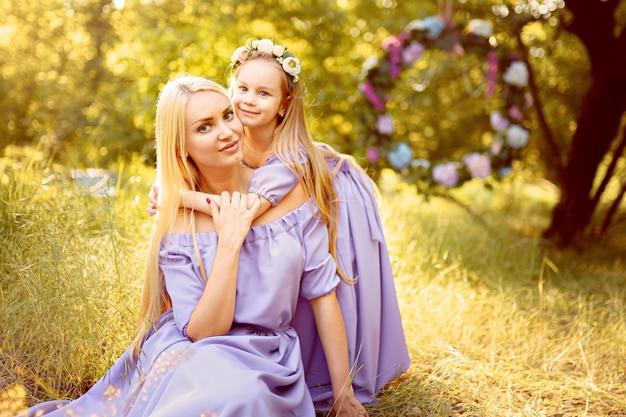 Mode buitenfoto van prachtige familie ziet er mooie moeder uit