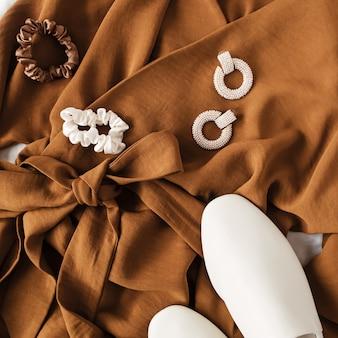 Mode collage met dameskleding en accessoires. bruine jurk, witte leren pantoffels, oorbellen