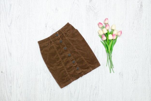 Mode concept. bruine velours rok en roze tulpen. hout achtergrond