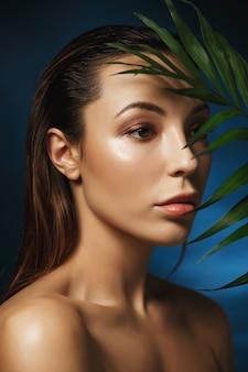Mode concept. close-up van geweldige vrouw op donkerblauwe muur met bladeren
